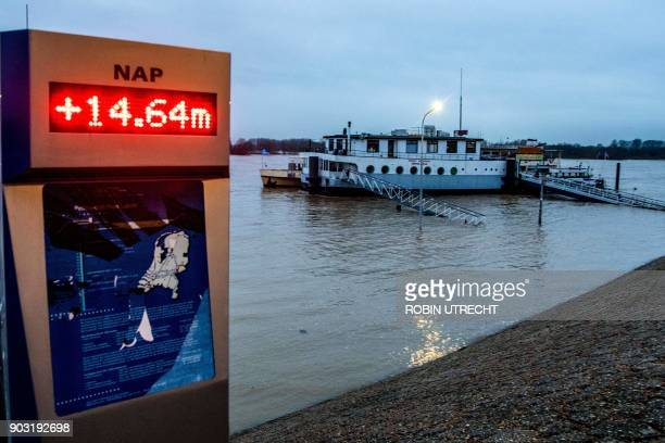 A picture taken on January 10 2018 shows a sign inidicating the water level in the Rhine at Lobith 1464 meter above NAP in Tolkamer After heavy rains...