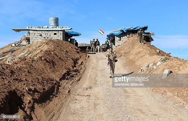 Picture taken on January 11, 2016 shows Kurdish peshmerga forces monitoring trenches they dug in the area of the district of Daquq, south of the...