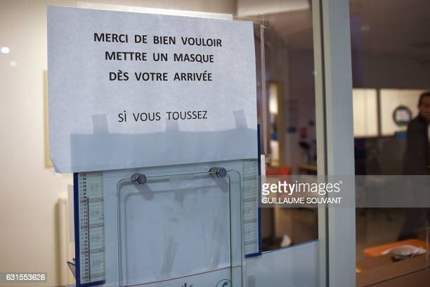 A picture taken on January 12 2017 shows a note which transaltes as 'Thank you for wearing a mask when at your arrival if you cough' at the emergency...