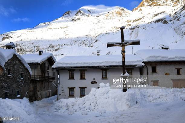 A picture taken on January 12 2018 shows a Christian cross in a snowy street in the centre of Bessans village in the French Alps / AFP PHOTO /...
