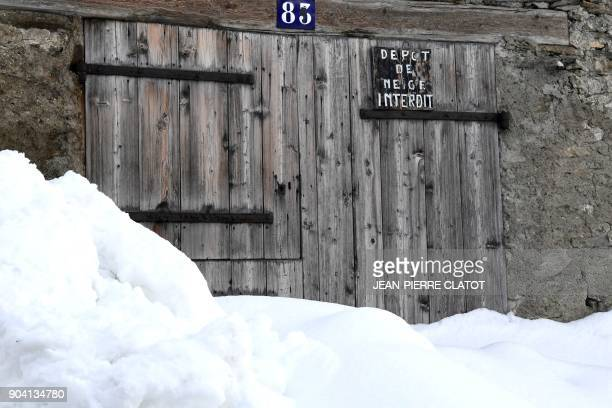 A picture taken on January 12 2018 shows a door with a sign reading 'snow deposit prohibited' in a snowy street in the centre of Bessans village in...