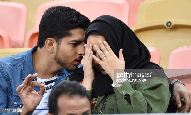 Picture taken on January 12, 2020 shows a Saudi couple attending a football match at King Abdullah Sport City Stadium in Jeddah. - In Saudi Arabia's...
