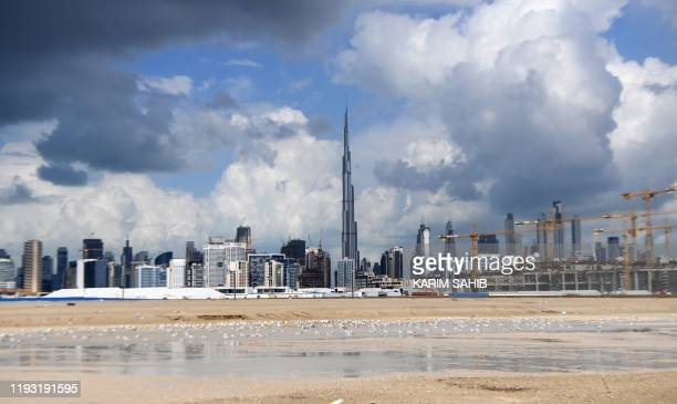 A picture taken on January 12 2020 shows dark clouds over the skyline of Dubai with Burj Khalifa the worlds tallest building