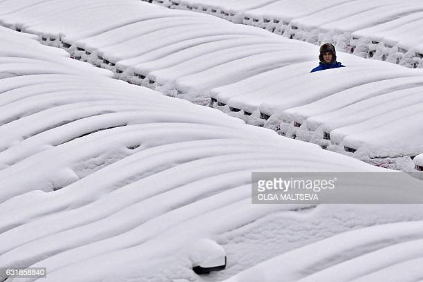 A picture taken on January 16 2017 shows a man standing among snowcovered locally assembled Hyundai cars parked near the carmaker's plant outside...