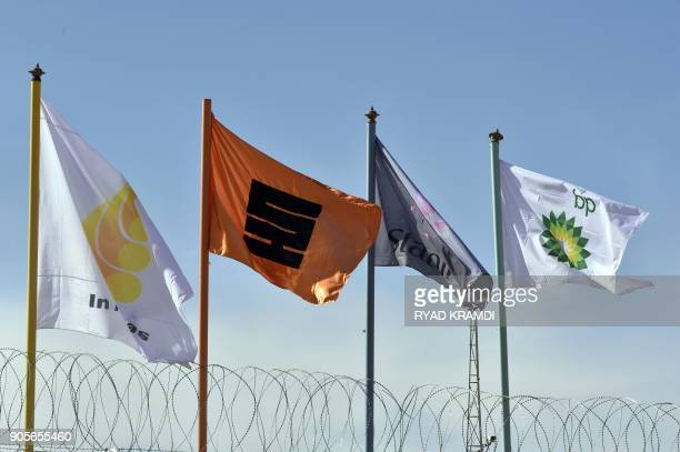A picture taken on January 16 2018 at In Amenas gas plant300 kilometres southeast of Algiers shows flags of various companies during a ceremony to...