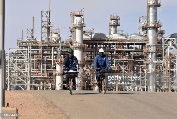 A picture taken on January 16 2018 at In Amenas gas plant300 kilometres southeast of Algiers shows workers riding bikes following a ceremony to mark...
