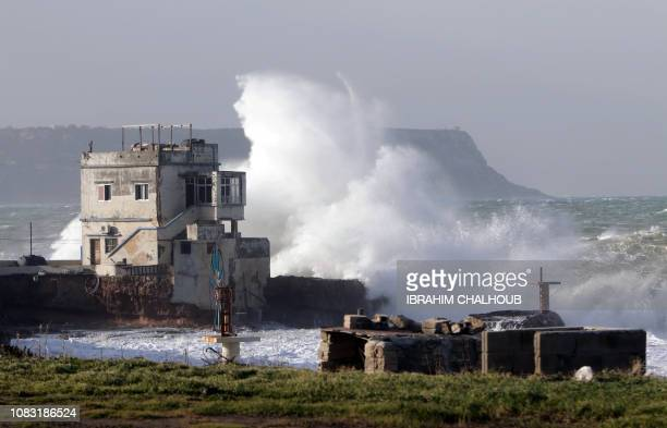 A picture taken on January 16 2019 shows waves breaking against a building on the shore in the northern Lebanese seaside town of Anfeh 65 Kms north...