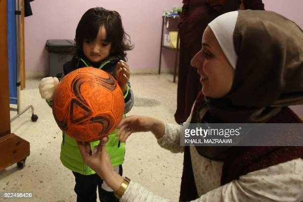 A picture taken on January 16 shows threeyearold child Ruwayd using her new prosthetic arm to play at the Doctors Without Borders reconstructive...