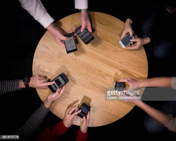 A picture taken on January 17 2017 in Paris shows people holding their cell phones The French law giving workers 'the right to disconnect' goes into...