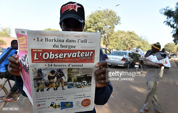 Picture taken on January 18, 2016 shows a man reasing a newspaper in the streets of Ouagadougou, following the jihadist attack claimed by Al-Qaeda in...