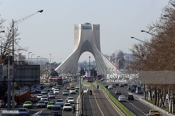 A picture taken on January 18 2016 shows vehicles driving on a street in front of the Azadi Tower in the capital Tehran KENARE