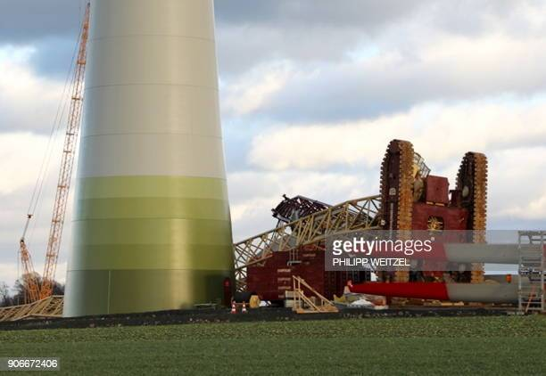 A picture taken on January 18 2018 shows a 150meterhigh crane on the ground near a wind turbine after it fell down due to strong winds in Kirtorf...
