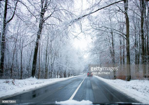 A picture taken on January 18 2018 shows a car driving on a road in a snowcovered landscape near Warin in northern Germany as the traffic is...