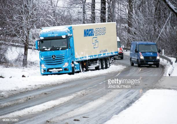 A picture taken on January 18 2018 shows a truck on the side of a road covered with snow near the municipality of Langen Bruetz in northern Germany...