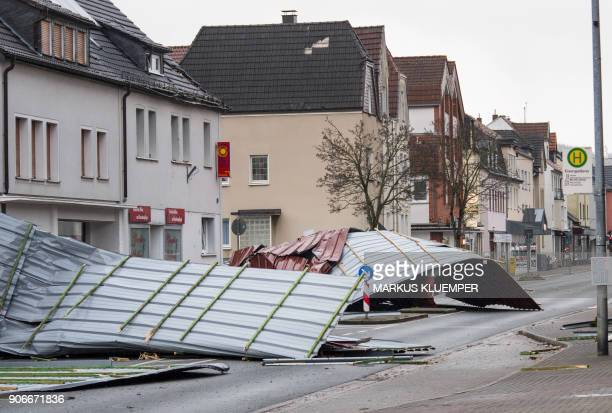 A picture taken on January 18 2018 shows metal roofing sheets from a supermarket blocking a road in Menden western Germany as the region is hit by...