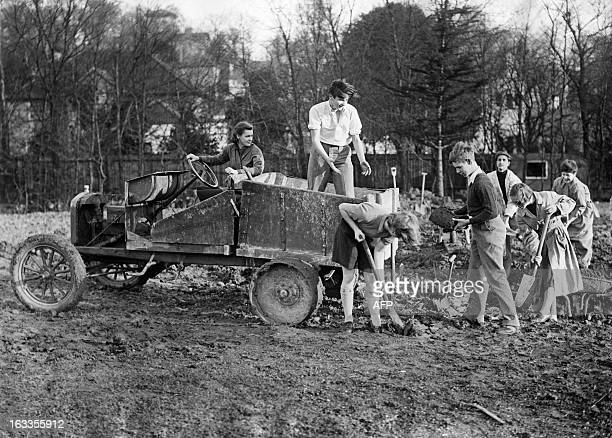 A picture taken on January 19 1938 in London shows teachers and pupils of the Beltane School levelling the school ground with the help of a converted...