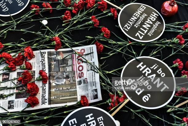 A picture taken on January 19 2018 shows placards reading 'We all are Hrant we all are Armenians' and red carnations in front of the offices of...
