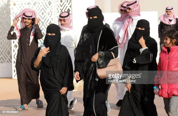 A picture taken on January 19 2018 shows Saudi women and men walking during the King Abdulaziz Camel Festival in Rumah some 160 kilometres east of...