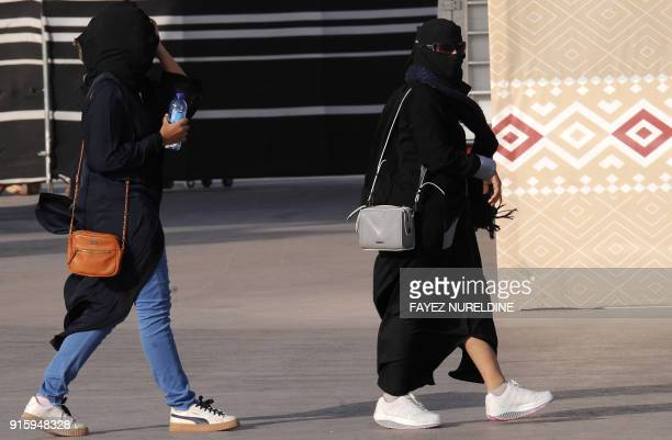 A picture taken on January 19 2018 shows Saudi women walking during the King Abdulaziz Camel Festival in Rumah some 160 kilometres east of Riyadh For...