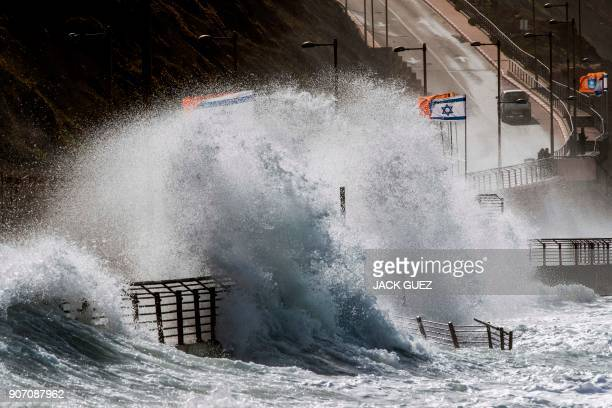 TOPSHOT A picture taken on January 19 2018 shows waves beating against a highway during a winter storm as Israeli flags flutter in the Mediterranean...