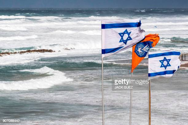 A picture taken on January 19 2018 shows waves beating against the shore during a winter storm as Israeli flags flutter in the Mediterranean coastal...