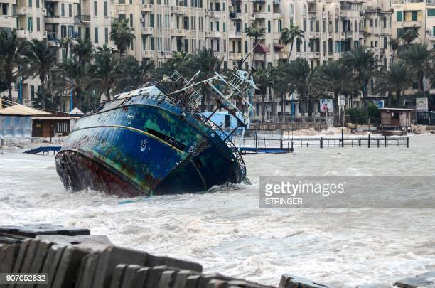 TOPSHOT A picture taken on January 19 2018 shows waves breaking against the hull of a ship on the shore of the Egyptian port city of Alexandria...