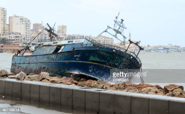 A picture taken on January 19 2018 shows waves breaking against the hull of a ship on the shore of the Egyptian port city of Alexandria during the...