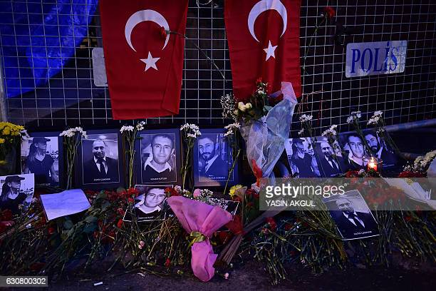 A picture taken on January 2 2017 in Istanbul shows portraits of victims laid in front of the Reina night club one day after a gunman killed 39...