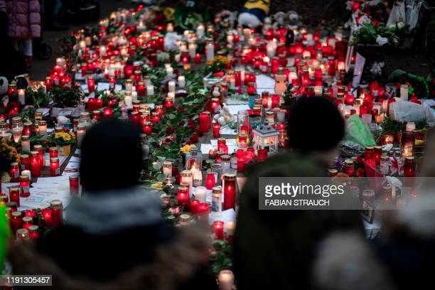 A picture taken on January 2 2020 shows flowers and candles left at a makeshift memorial site in front of the burnedout monkey house at Krefeld zoo...