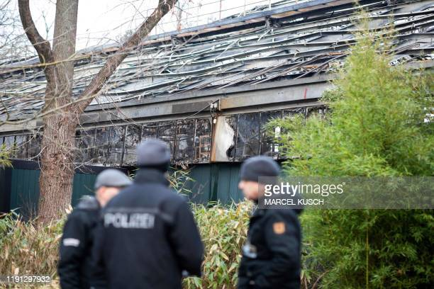 A picture taken on January 2 2020 shows police standing in front of the burnedout monkey house at Krefeld zoo western Germany after a fire on New...