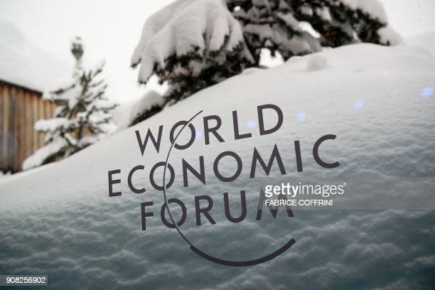 A picture taken on January 21 2018 shows the logo of the World Economic Forum under the snow on the eve of the opening day of the WEF 2018 annual...