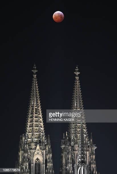 A picture taken on January 21 2019 in Cologne shows a view of the Super Blood Moon above the landmark Dome during a lunar eclipse / Germany OUT