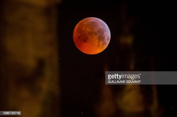 A picture taken on January 21 2019 shows the socalled Super Blood Wolf Moon above the Tours's cathedral on January 21 central France