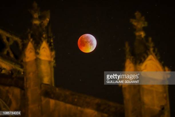 TOPSHOT A picture taken on January 21 2019 shows the socalled Super Blood Wolf Moon behind the Tours's cathedral on January 21 central France
