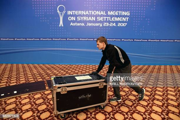 TOPSHOT A picture taken on January 22 2017 shows a man at work to prepare the Syria peace talks conference room at Astana' Rixos President Hotel The...