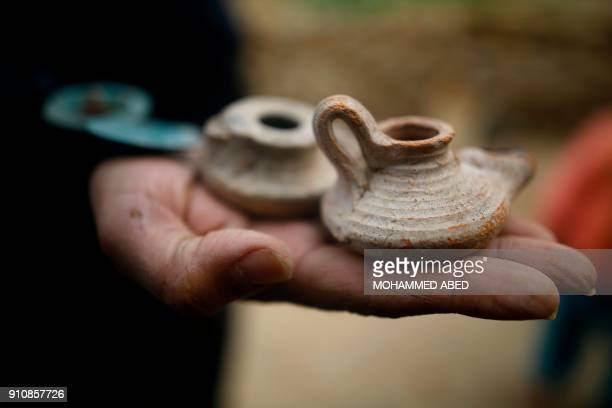 A picture taken on January 26 2018 shows recovered small pottery items found at a freshlydiscovered cemetery in the garden of a house in Beit Hanun...