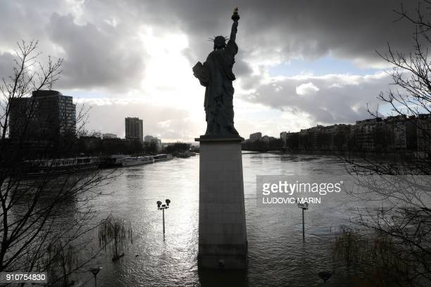 TOPSHOT A picture taken on January 26 shows the flooded Ile aux Cygnes and banks of the river Seine with a model of the Statue of Liberty in Paris...