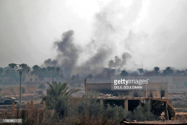 A picture taken on January 27 2019 in the Syrian village of Baghouz shows smoke billowing from a spot where Arab and Kurdish fighters from the Syrian...