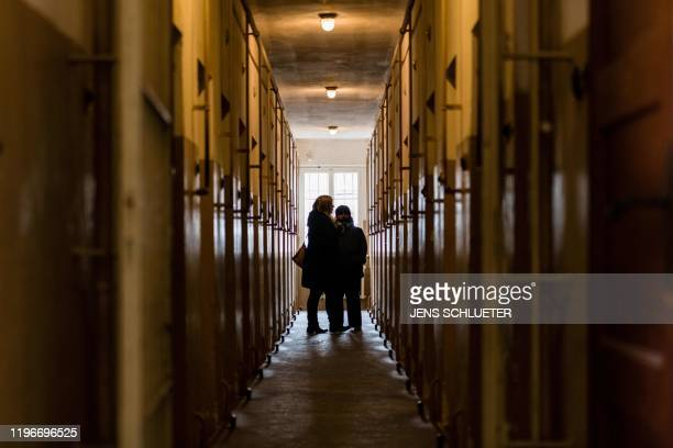 A picture taken on January 27 2020 shows visitors in a corridor with cells at the memorial site of the former Nazi concentration camp Buchenwald near...