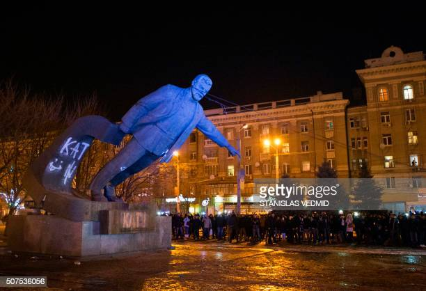A picture taken on January 29 2016 shows Ukrainian Nationalists supported by a cheering crowd preparing to torn down the statue of early Communist...