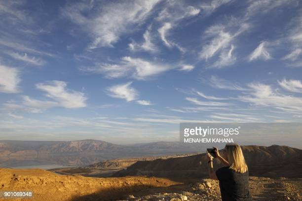 A Picture taken on January 3 2018 shows a tourist taking a photo of evaporation ponds at the southern part of the Dead Sea where both sodium chloride...