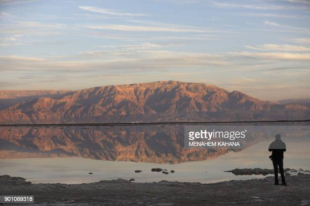 Picture taken on January 3 2018 shows a tourist walking next to evaporation ponds in the southern part of the Dead Sea where both sodium chloride and...