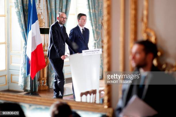 A picture taken on January 3 2018 shows the reflection in the mirror of French Prime Minister Edouard Philippe delivering a speech next to the...