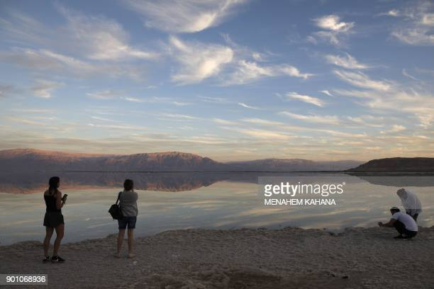 A Picture taken on January 3 2018 shows tourists walking next to evaporation ponds in the southern part of the Dead Sea where both sodium chloride...