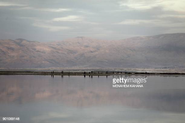 A Picture taken on January 3 2018 shows tourists walking on a dirt embankment between evaporation ponds in the southern part of the Dead Sea where...