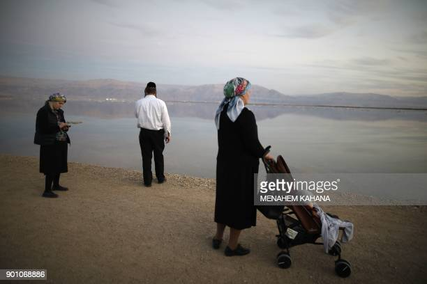 A Picture taken on January 3 2018 shows UltraOrthodox Jews walking next to evaporation ponds in the southern part of the Dead Sea where both sodium...