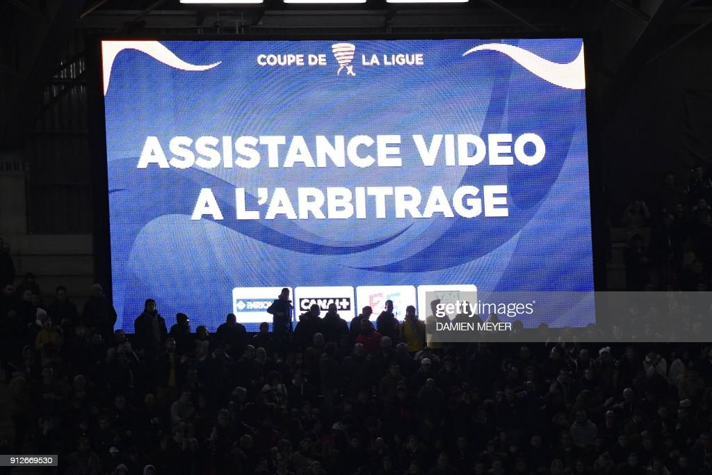 A picture taken on January 30, 2018 shows a video screen reading 'Video assistance to the refereeing' during the French League Cup football semi-final match between Rennes and Paris Saint-Germain at the Roazhon Park stadium in Rennes on January 30, 2018. With two goals denied, a yellow card that passed to red, the refereeing video held a prominent place in the semi-final football match of the French League Cup. /