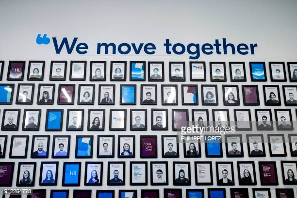 A picture taken on January 30 2018 shows a wall with the employees identity picture in the lobby of BlaBlaCar headquarters in Paris The carpool...
