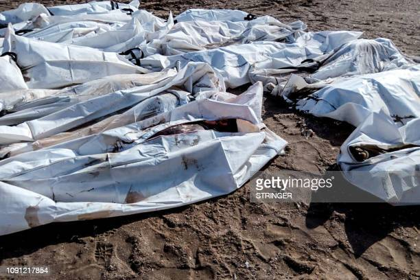 A picture taken on January 30 shows bodies in body bags collected on beach in Obock Djibouti after two migrant boats capsized off the coast The death...