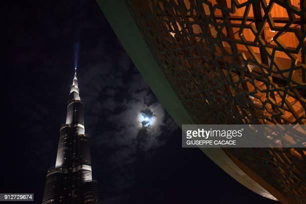 A picture taken on January 31 2018 shows a 'supermoon' rising behind Dubai's Burj Khalifa / AFP PHOTO / GIUSEPPE CACACE